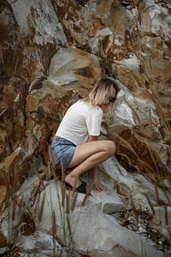 Side view of young woman on rock