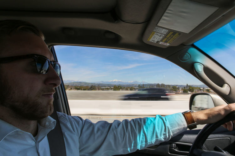 Car Car Interior Close-up Day Driving Eyeglasses  Headshot Land Vehicle Lifestyles Men Mode Of Transport Mountains In Background One Person Outdoors Real People Sky Steering Wheel Sunglasses Transportation Young Adult