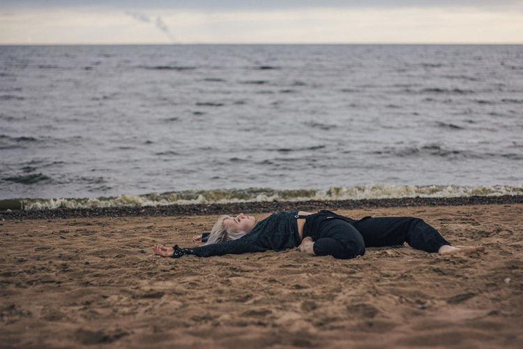 Man lying on shore at beach against sky