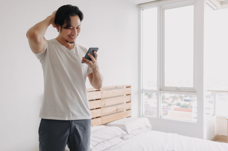 Young man using mobile phone while sitting on bed