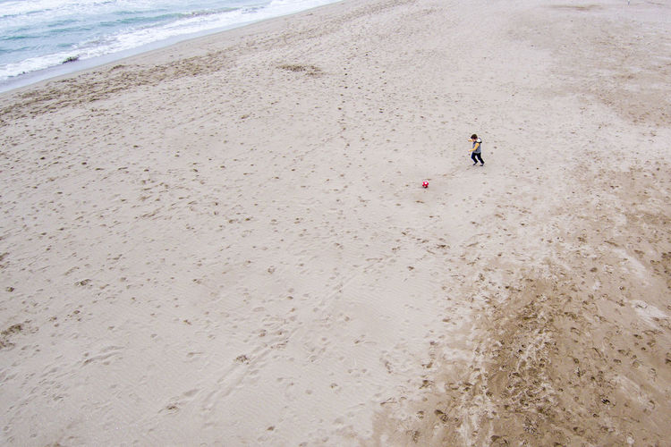 High angle view of boy playing soccer on sand at beach