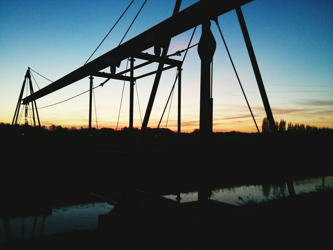 silhouette, sunset, water, reflection, sky, connection, bridge - man made structure, outdoors, no people, river, tranquility, tranquil scene, travel destinations, nature, scenics, landscape, tree, architecture, clear sky, beauty in nature, day