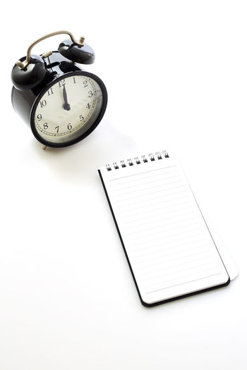 Black alarm clock with blank white notebook on white background, concept back to school School Notebook Business Workplace Office Object Clock Alarm White Space Background View Top Blank Desk Copy Table Empty Pencil Design Paper NotePad Work Time Pen Note Concept Flat Lay Book Wooden Black Education Computer Sport Laptop Keyboard Digital Retro Weight White Background Studio Shot Still Life Indoors  Copy Space No People Publication Close-up Spiral Notebook Number High Angle View Communication Single Object Cut Out Accuracy Clock Face Personal Accessory Minute Hand