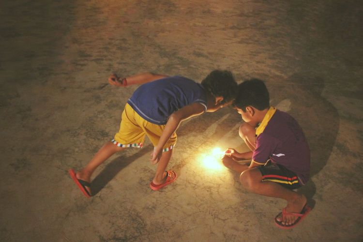 High Angle View Of Boys Burning Cracker During Diwali At Night