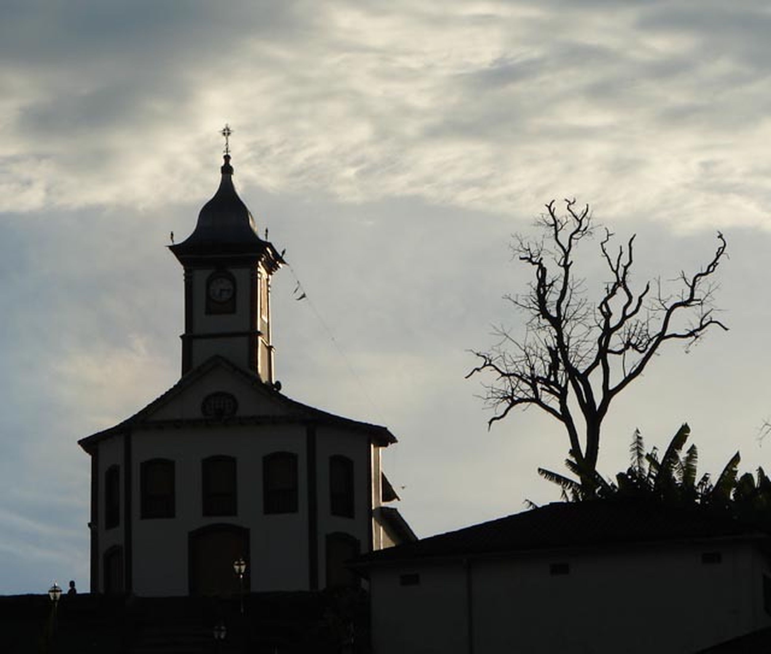 building exterior, architecture, low angle view, built structure, church, sky, religion, place of worship, spirituality, cloud - sky, silhouette, tree, cross, cloud, high section, cloudy, outdoors, bare tree