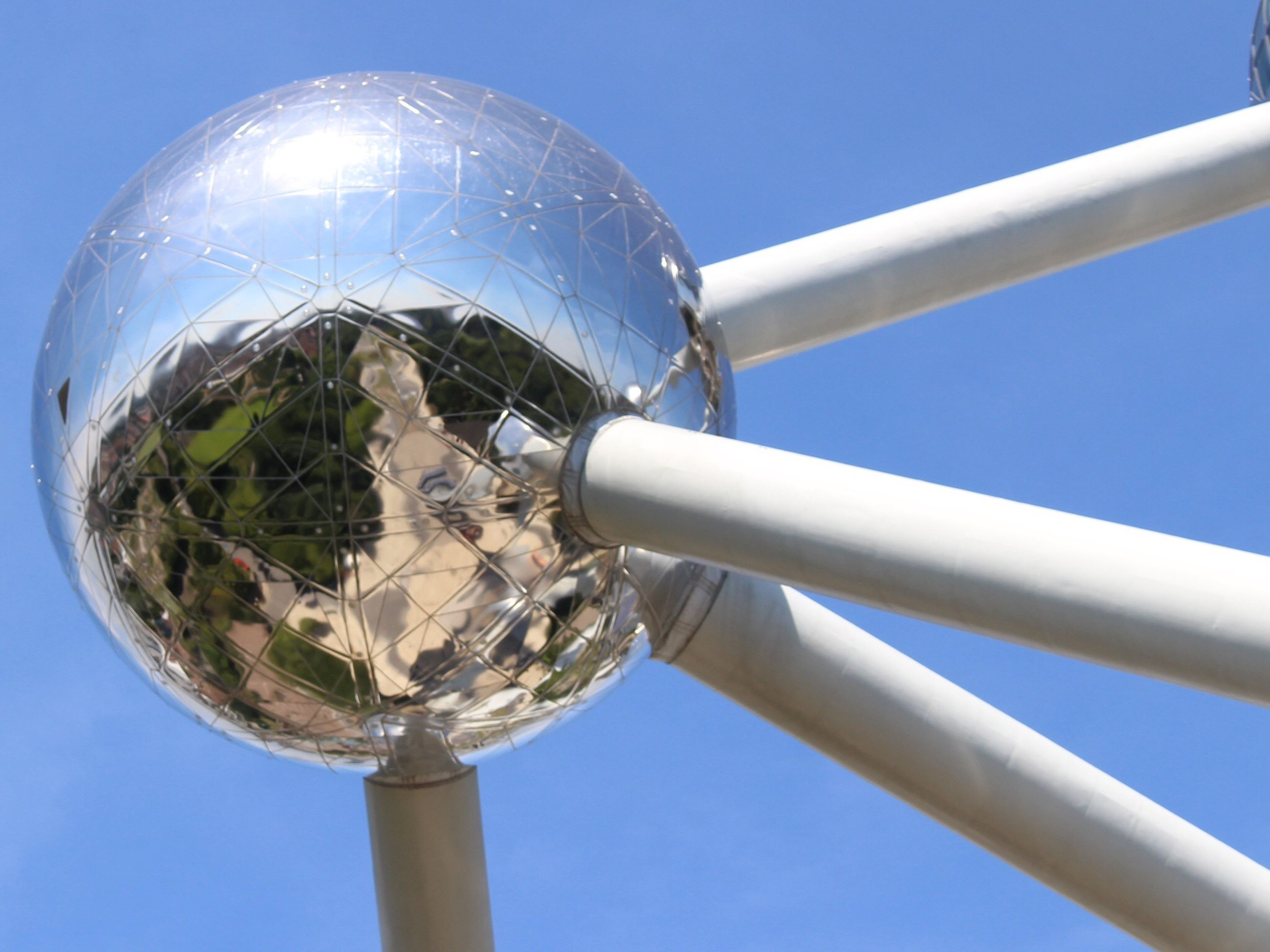 low angle view, blue, clear sky, built structure, architecture, sphere, close-up, sky, glass - material, street light, metal, day, no people, lighting equipment, outdoors, transparent, building exterior, sunlight, tower, copy space