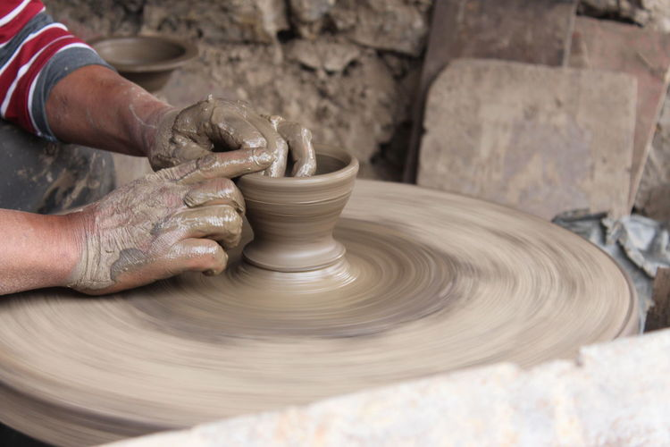 Midsection of man working with mud on pottery wheel