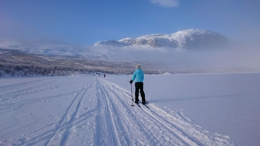 Rear view of person skiing on snowy field against cloudy sky during sunny day