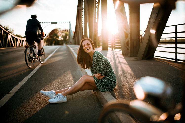 Woman riding bicycle on road in city