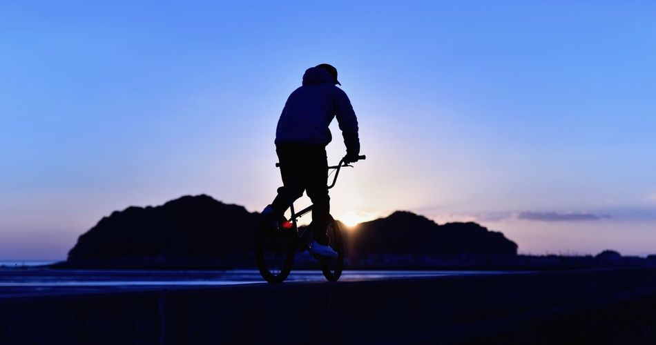 Full length of man cycling at beach against sky during sunset