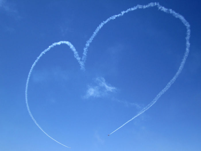 Low angle view of smoke forming heart shape in blue sky