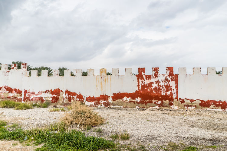 Peeled wall on landscape against clouds