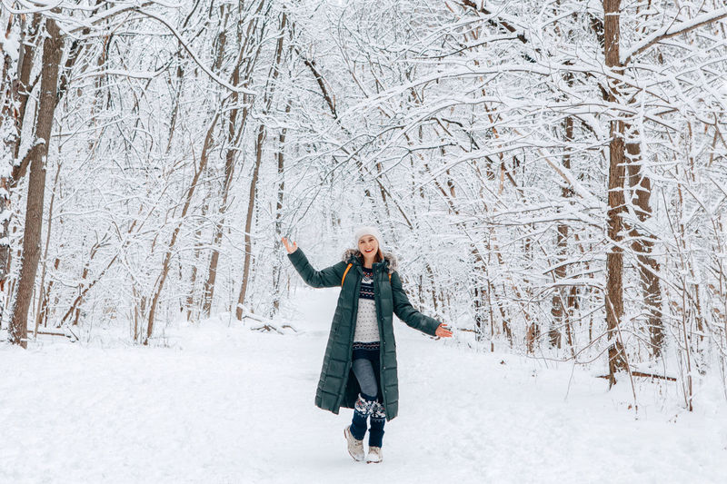 Woman in winter clothes and hat walking wandering in park forest outdoor on winter day