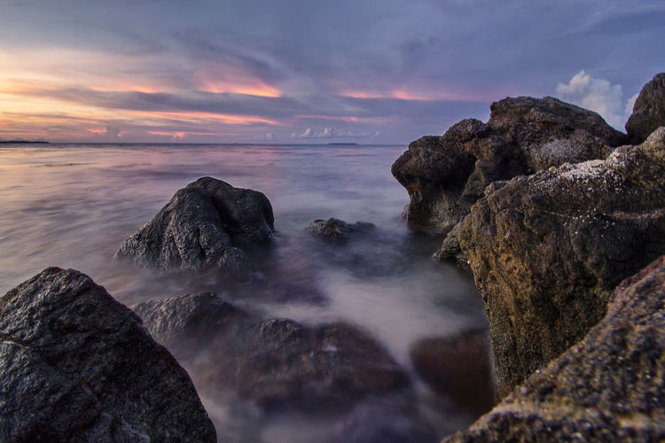 A dusk at ujung gelam beach. scenic view of sea against sky during sunset