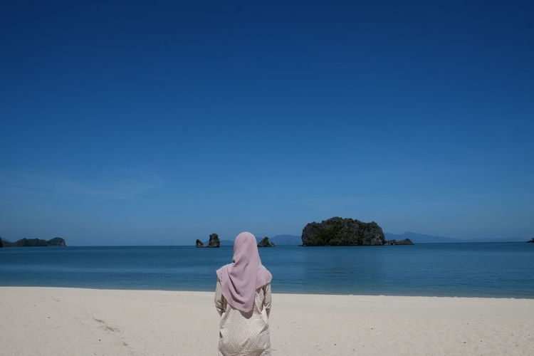 Rear View Of Woman On Beach Against Clear Blue Sky