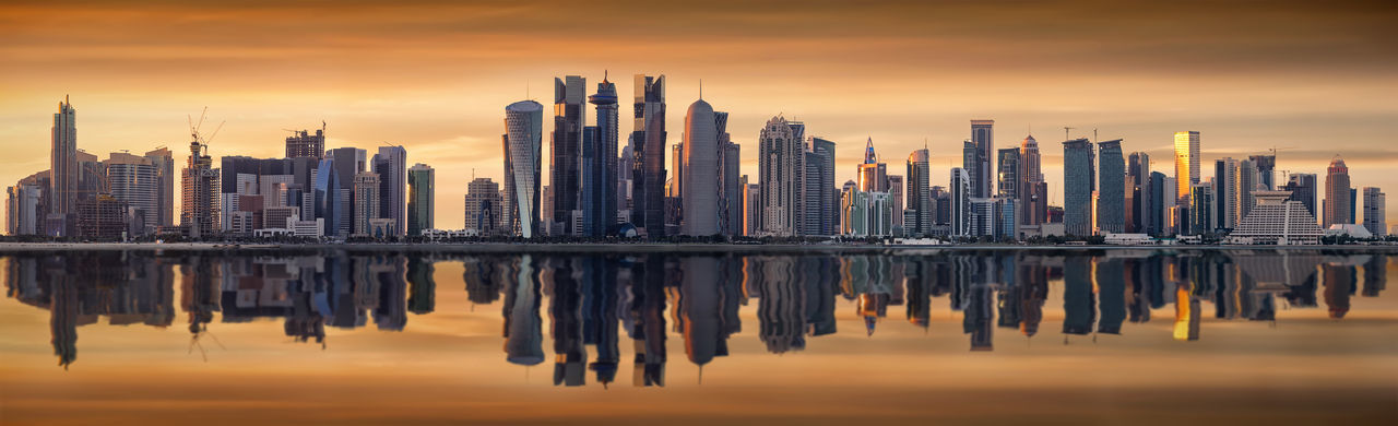 The modern skyline of Doha, Qatar, during sunset Doha Middle East Modern Panorama Rich Skyline Tourist Attraction  Travel Water Reflections Architecture Bay City Cityscape Cloud - Sky Modern Qatar Reflection Scenics Sky Skyscraper Sunset Travel Destinations Urban Skyline Water Waterfront