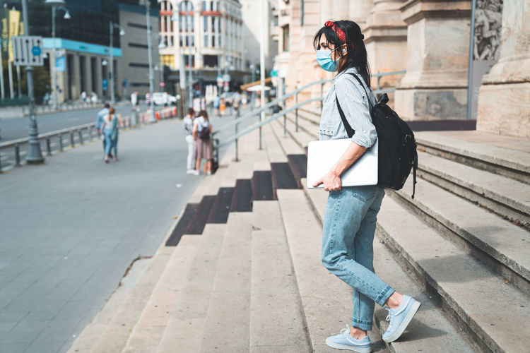 Full length of woman on footpath in city