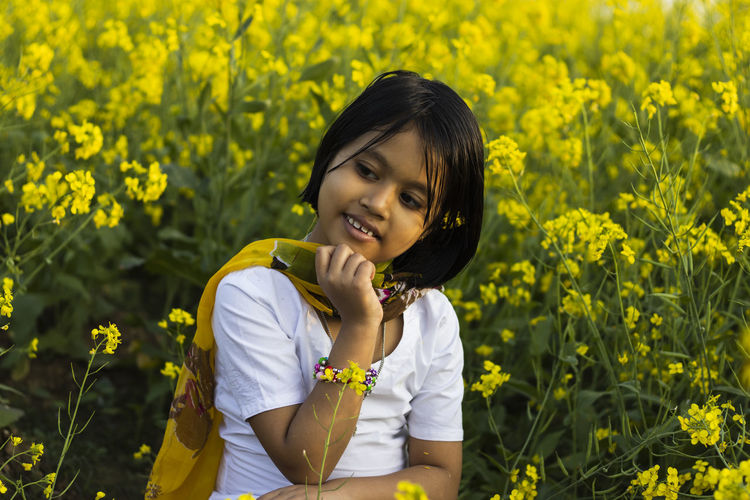 A beautiful innocent indian girl child in white dress sitting near yellow mustard flower field