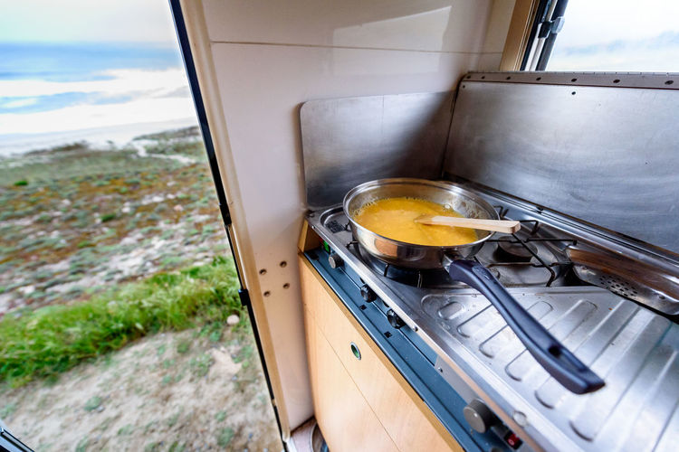 Close-Up View Of Food In Saucepan On Stove At Campervan
