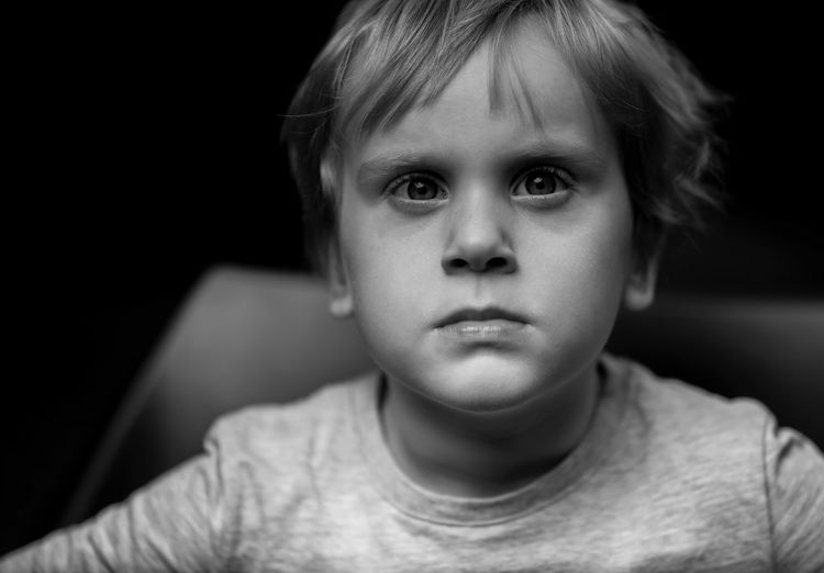Close-up portrait of boy sitting on chair against black background
