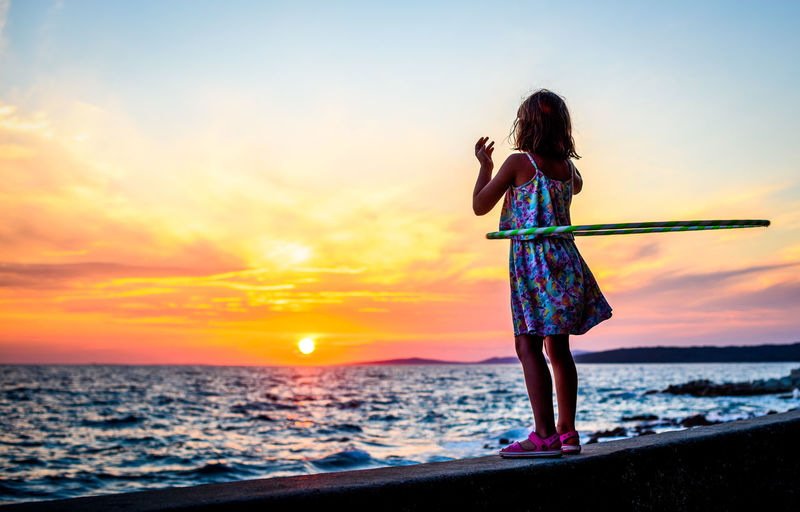 Full length of girl playing with hula hoop on shore at beach against sky during sunset
