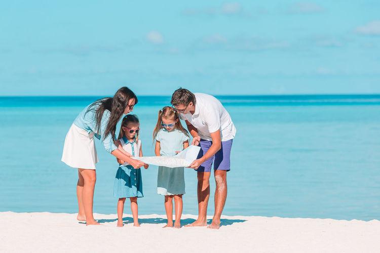 Full length of family standing on beach against sky