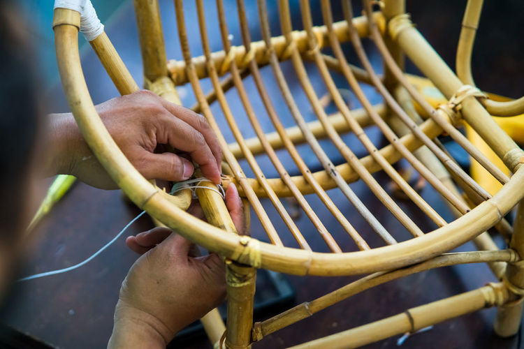 Close-up of man making wicker chair