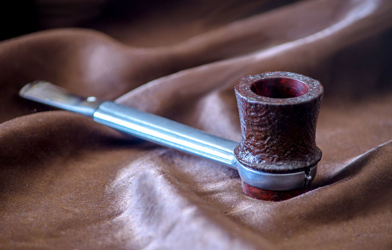 Close-up of smoking pipe on brown leather
