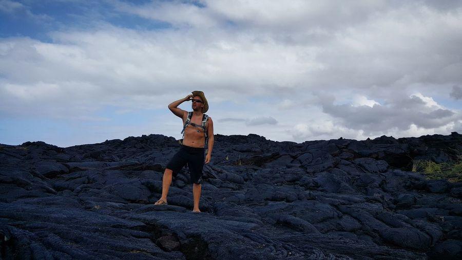 Man looking away standing on rocks against sky
