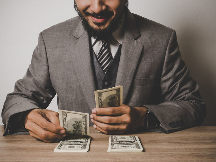 Midsection Of Smiling Businessman With Paper Currency At Table
