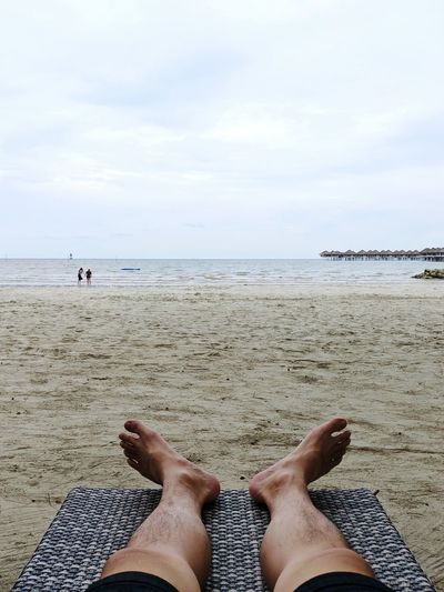 Low section of person relaxing on beach against sky