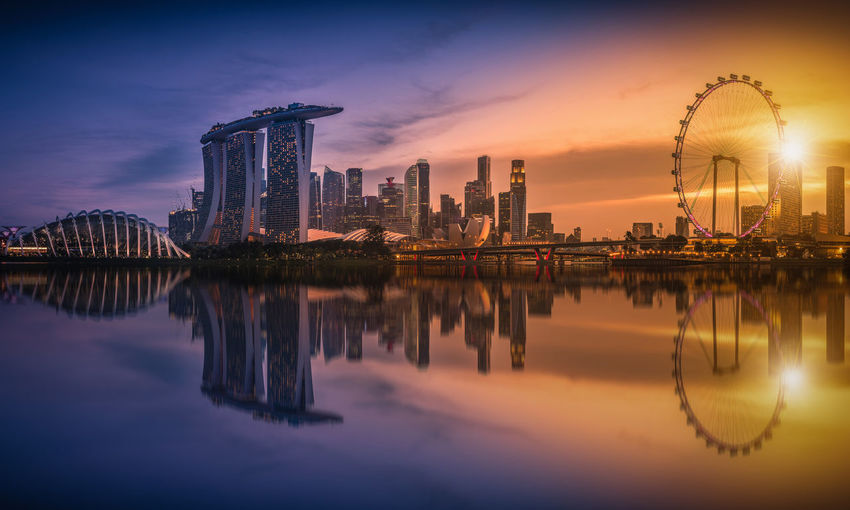 Marina bay sands by bay of water in city during sunset