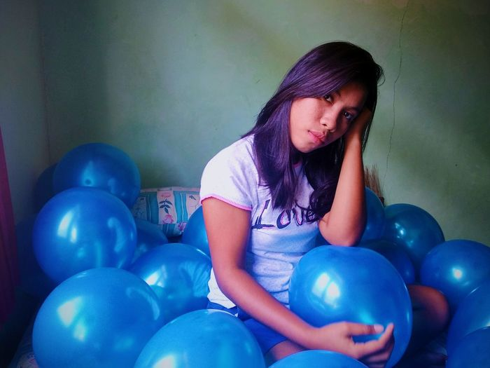 Portrait of young woman with blue balloons sitting at home