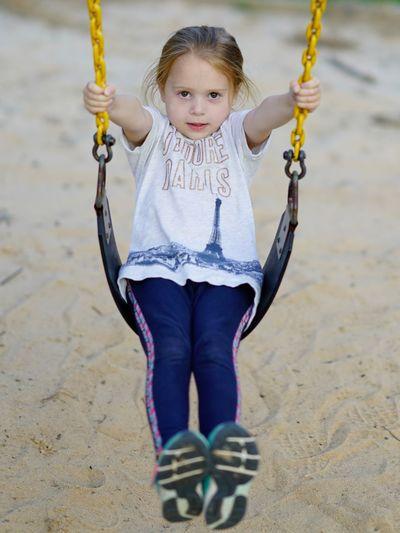 Girl swinging over sand in park