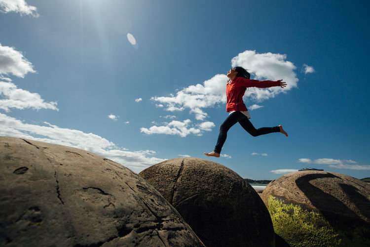 Low angle view of man jumping on rock against sky