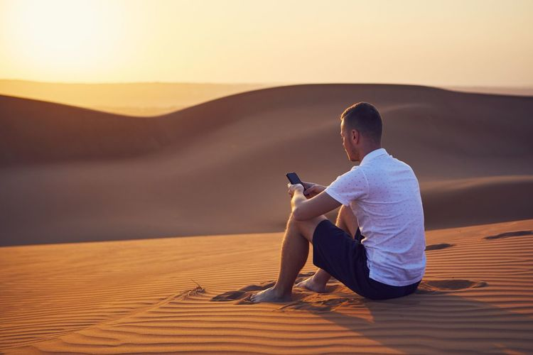 Full length of man using phone while sitting on sand