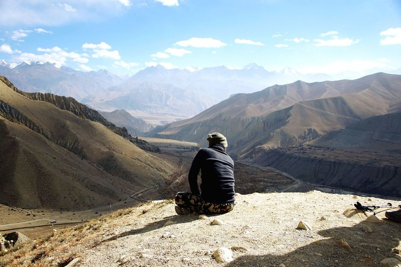 High above the mountain desert. Mustang Himalayas Hikers Nepal EyeEm Selects Mountain Rear View One Person Real People Leisure Activity Beauty In Nature Mountain Range Lifestyles Scenics - Nature Nature Tranquil Scene Sunlight Tranquility Sitting Day Non-urban Scene Landscape Holiday Outdoors