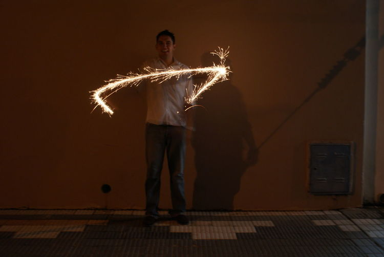 Full length portrait of man holding illuminated sparkler against wall at night