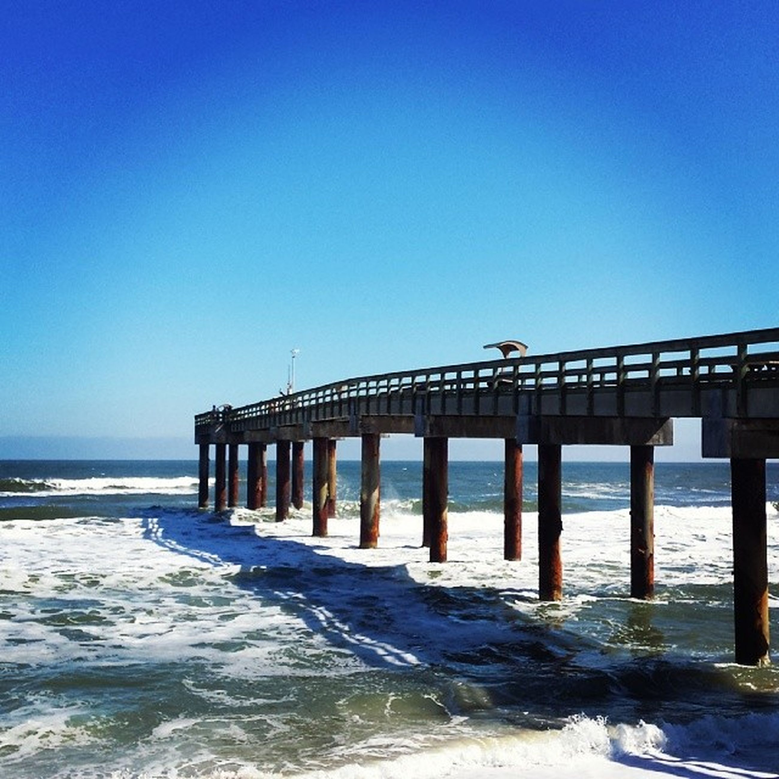 sea, water, clear sky, copy space, horizon over water, blue, beach, wave, pier, scenics, built structure, surf, nature, beauty in nature, tranquil scene, tranquility, shore, bird, architecture, waterfront