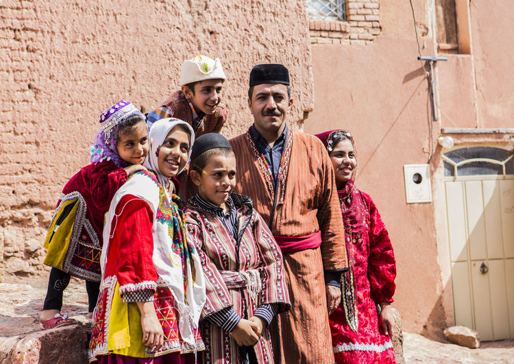 Happy family wearing traditional clothing standing against wall