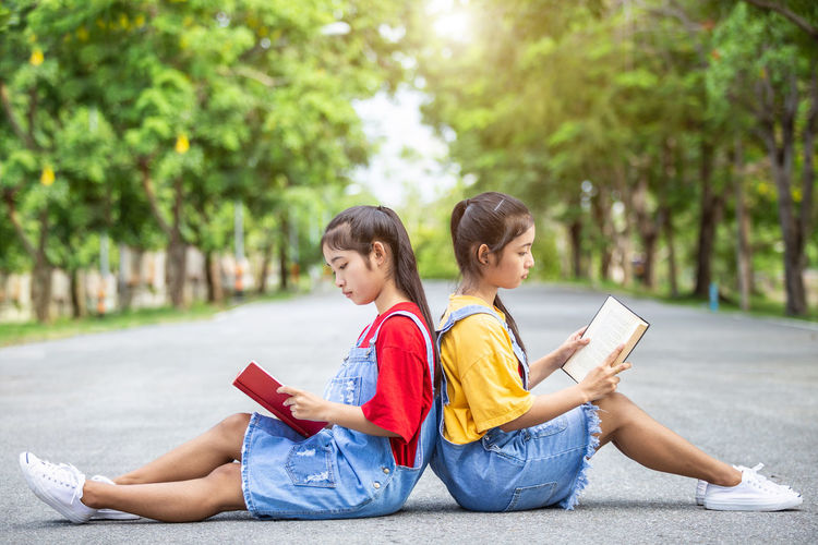 Two women sitting on book