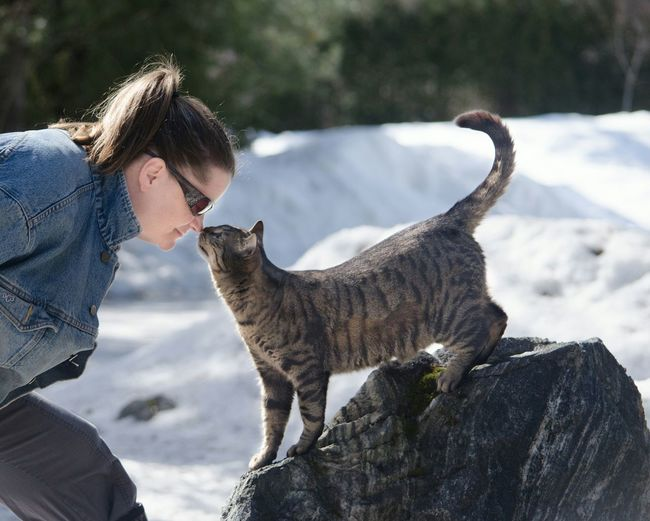 Woman Playing With Cat On Snowy Field