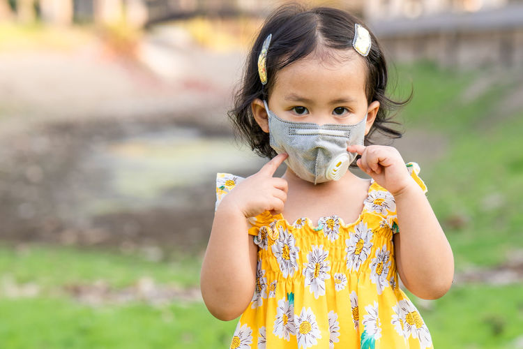 Cute girl standing outdoor wearing medical face mask to prevent flu, pollution and covid 19.