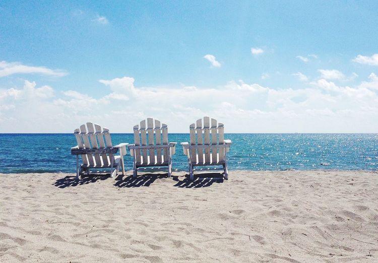 Empty adirondack chair on sand at beach against sky
