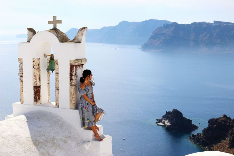 Woman leaning by cross against sea at santorini
