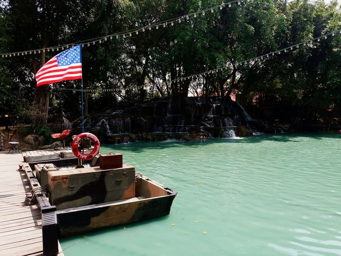Green lake with boat and American flagNature Tree Patriotism Water Outdoors No People Flag Day Lake Lakeside Boat Wooden Bridge American Flag Army Pathway Light Waterfall Blue Water Sea