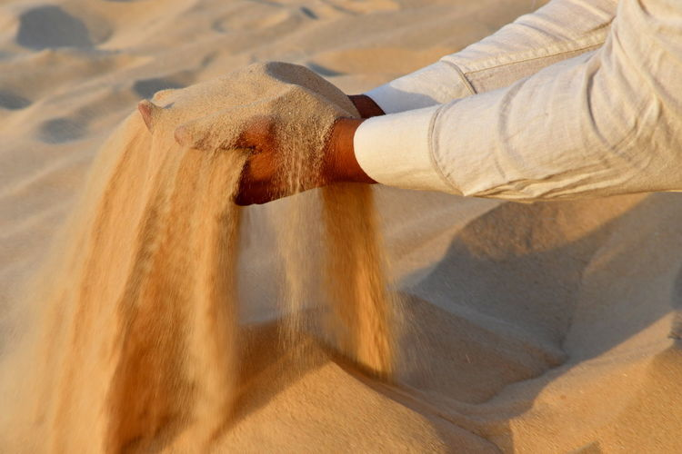 Cropped Hands Of Man Holding Sand At Desert