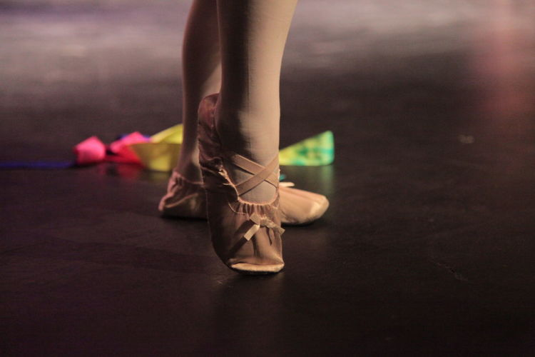 Low section of ballet dancer standing on stage