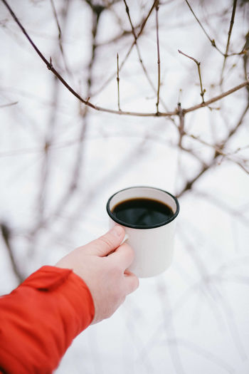 Cropped hand holding tea cup during winter