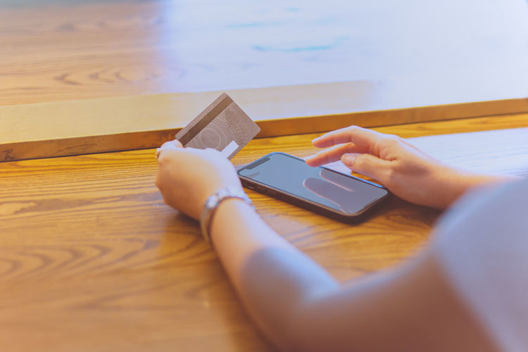 Midsection of person using mobile phone on table